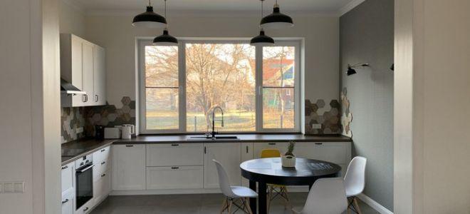Просторная белая угловая кухня-гостиная в частном доме с мойкой у окна