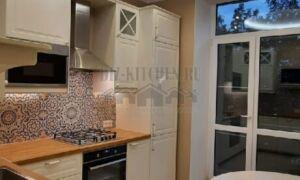 Белая кухня с деревянной столешницей и ярким фартуком