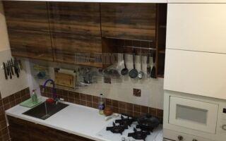 Кухня с деревянными секциями и барной стойкой, переходящей в полку