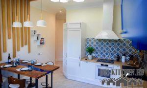 Оригинальная белая кухня с деревянной инсталляцией через стены и потолок