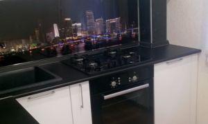 Дизайн белой кухни 5 кв.м с черной столешницей и холодильником в нише