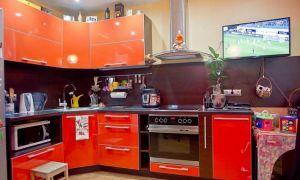 Оранжевая кухня площадью 12 кв.м с черным фартуком