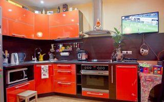 Оранжевая кухня площадью 12 м<sup>2</sup> с черным фартуком
