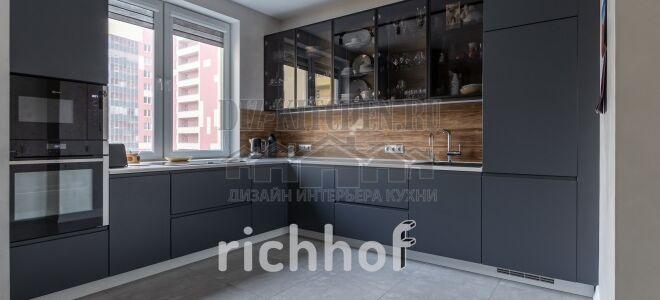 Современная кухня со стеклянными фасадами и варочной панелью под окном