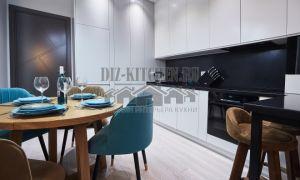 Белая кухня, разделенная барной стойкой, совмещенная с гостиной