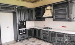 Строгая черная кухня из массива в загородном доме с резными фасадами