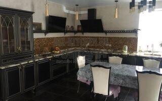 Черная классическая кухня с золотой отделкой, совмещенная с гостиной