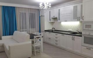 Интерьер белой кухни-гостиной 20 м<sup>2</sup> с черной столешницей и бирюзовыми шторами