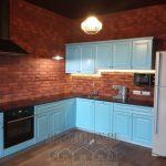 Голубая кухня 10 кв. м на фоне кирпичной стены в стиле фьюжн