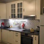 Маленькая белая неоклассическая кухня с кирпичным фартуком